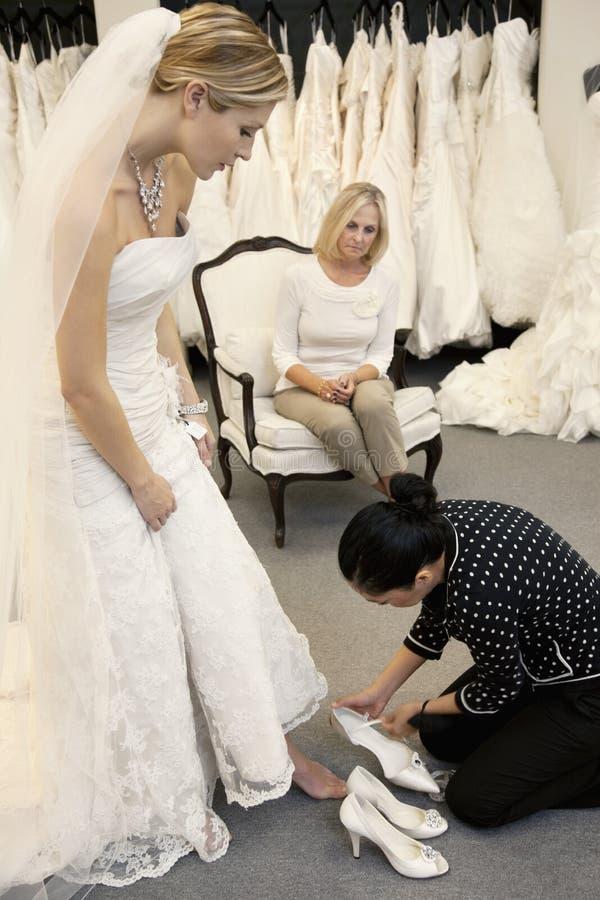 Fostra att se som kvinnlig anställd som hjälper den unga dottern i skodon royaltyfri foto