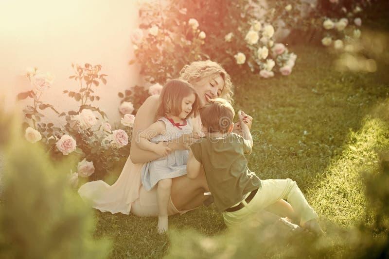 Fostra att spela med dottern och sonen i sommarträdgård royaltyfri fotografi