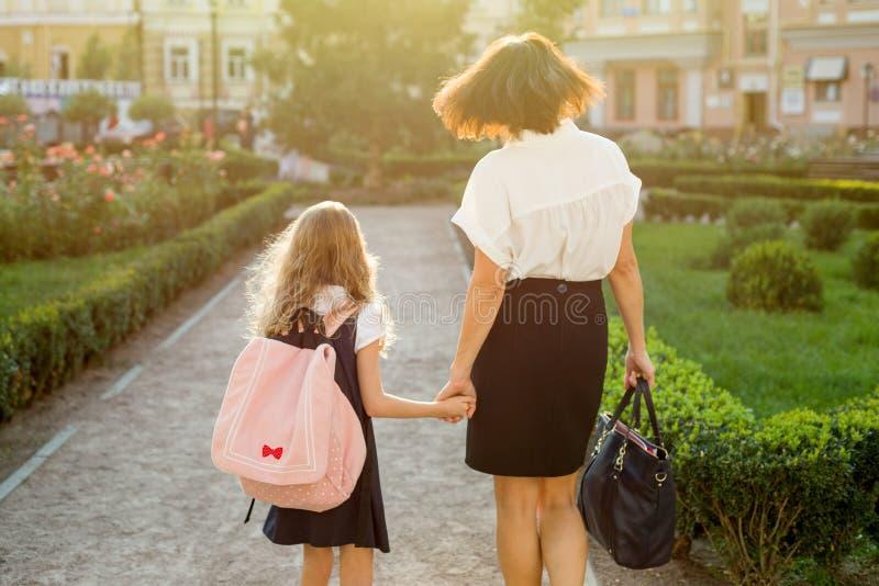 Fostra att ta dottern till skolan - tillbaka sikt royaltyfri fotografi