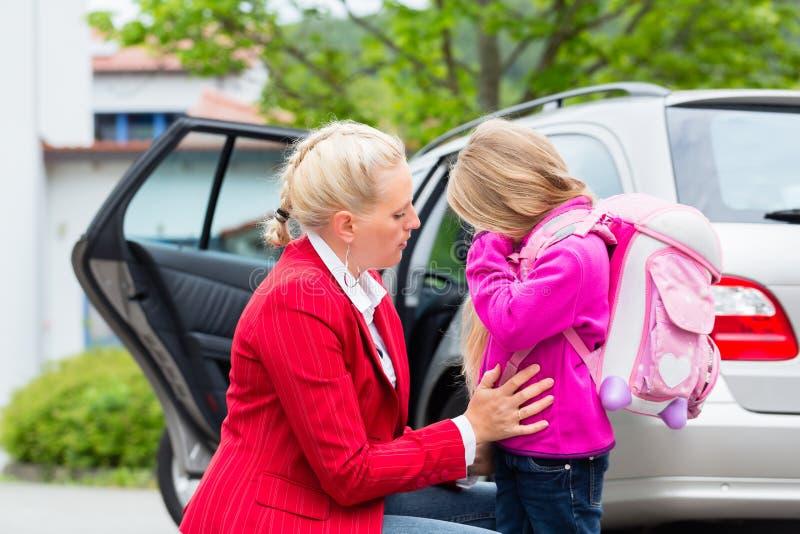 Fostra att trösta dottern på den första dagen på skolan royaltyfri bild