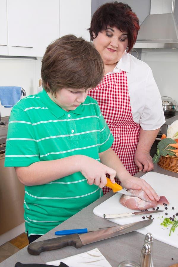 Fostra att undervisa hennes son att laga mat kött - fett och övervikt arkivbild