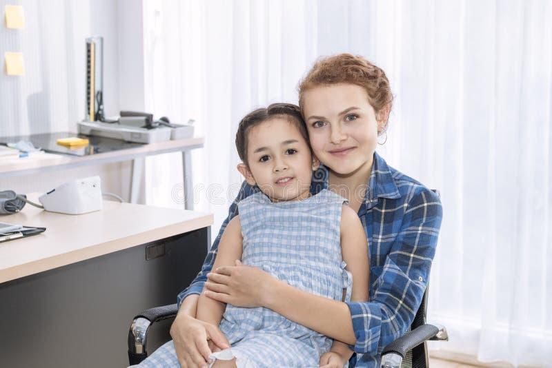 Fostra caucasianen och ungen som ler i sjukhusrum Väntande på doktor royaltyfria foton