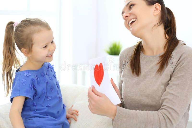 Fostra dagbegreppet för ` s Barndottern gratulerar mamman och ger hennes vykort med röd hjärtaform Lyckliga Mum och flicka arkivfoton