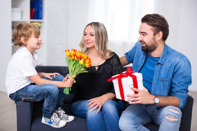 Fostra dagbegreppet för ` s - den lilla sonen och fadern som ger blommor och royaltyfri foto