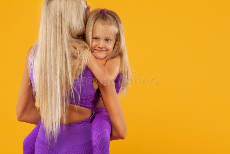 Fostra dagbegreppet för ` s Konditionfamiljblick Den barnmoderidrottsman nen och dottern övar tillsammans inomhus royaltyfria bilder