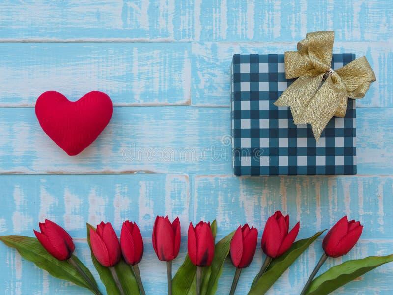 Fostra dagbegreppet för ` s röd hjärta, tulpan blommar och giftbox på p arkivbild