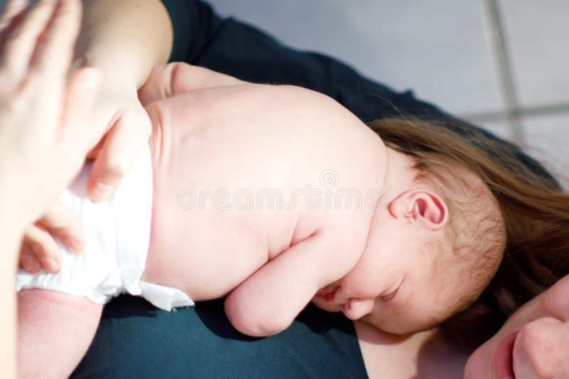 Fostra innehavet som hennes nyfött behandla som ett barn dottern efter födelse på armar arkivfoton