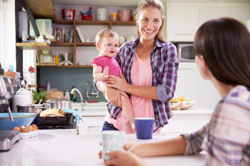 Fostra med den unga dottern som talar till vännen i kök arkivbild