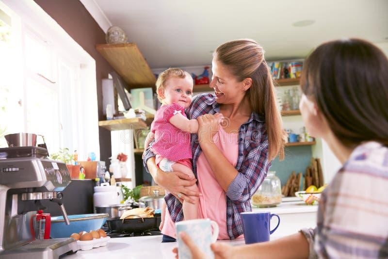 Fostra med den unga dottern som talar till vännen i kök royaltyfria bilder