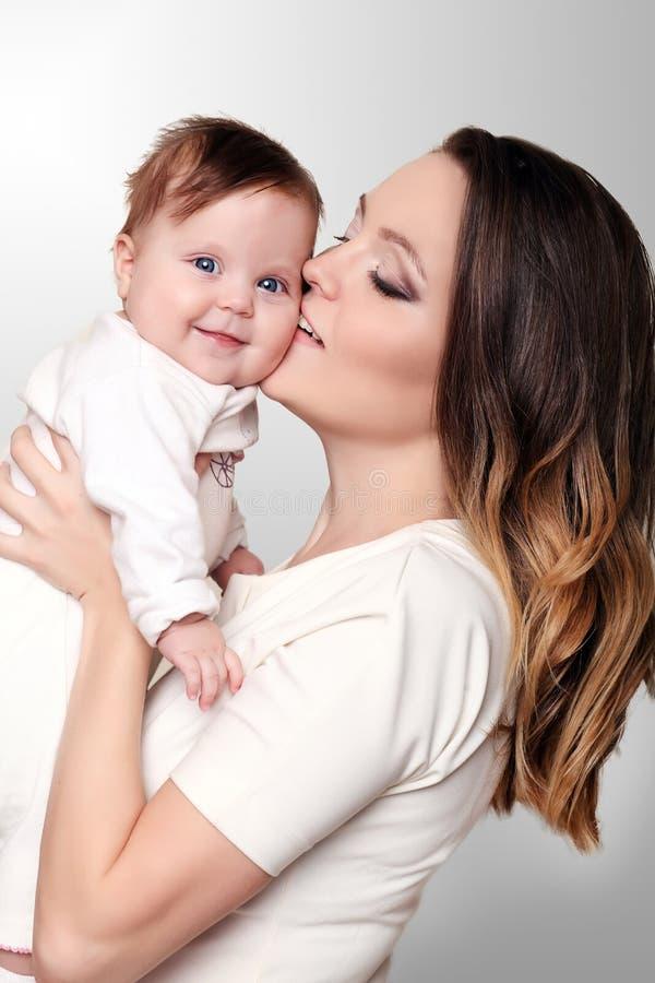 Fostra och behandla som ett barn att kyssa och att krama lycklig familj royaltyfri foto