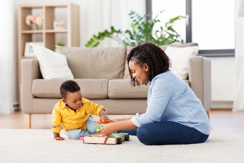 Fostra och behandla som ett barn att spela med leksakkvarter hemma royaltyfria foton