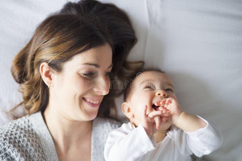 Fostra och behandla som ett barn barnet på en vit säng royaltyfria foton