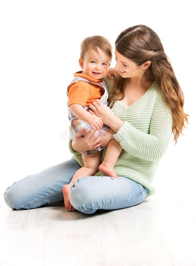 Fostra och behandla som ett barn, den lyckliga mamman med barnet, familj på vit arkivfoto