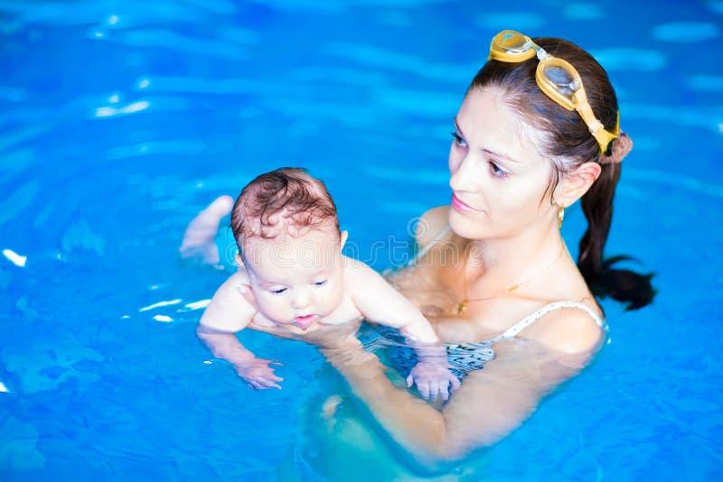 Fostra och behandla som ett barn flickan i simbassäng arkivbilder
