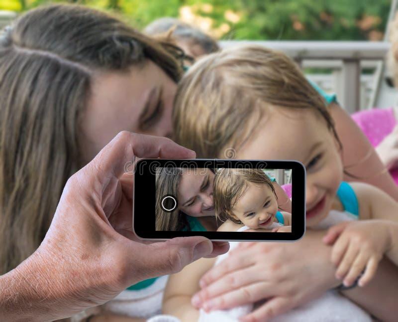 Fostra och behandla som ett barn flickan i smartphonekort royaltyfria bilder