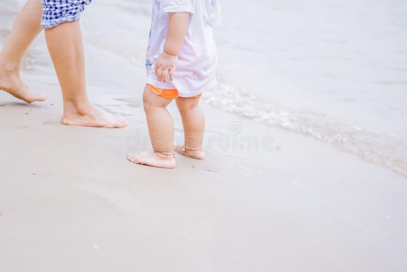 Fostra och behandla som ett barn fot som går på sandstranden arkivfoton