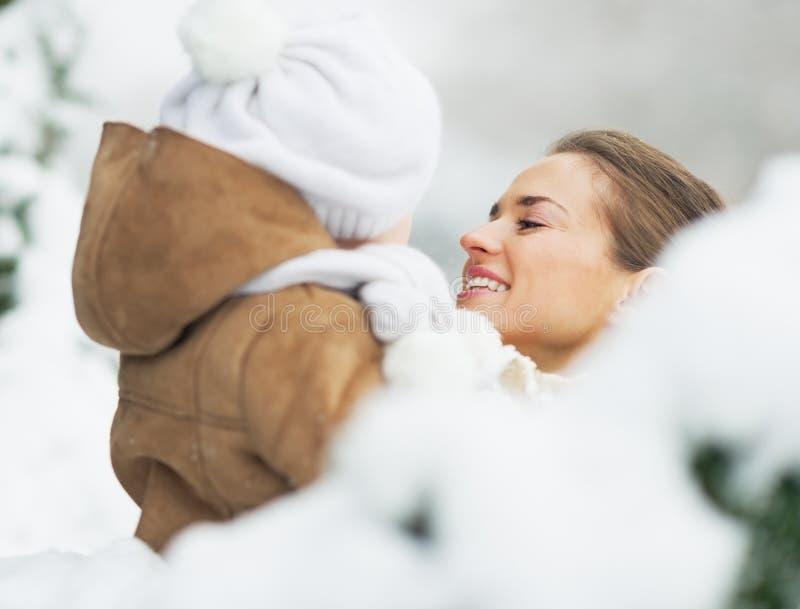 Fostra och behandla som ett barn i vinter parkerar bak snöig filialer fotografering för bildbyråer