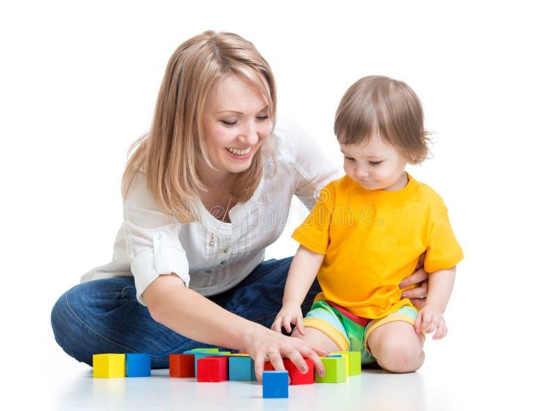 Fostra och behandla som ett barn lek med leksaken för byggnadskvarter arkivfoto