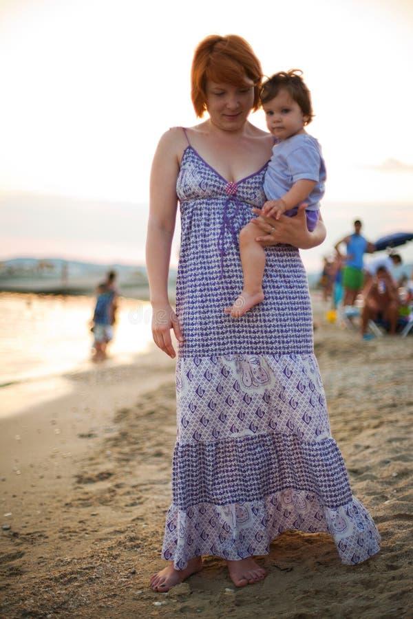 Fostra och behandla som ett barn på stranden arkivbilder