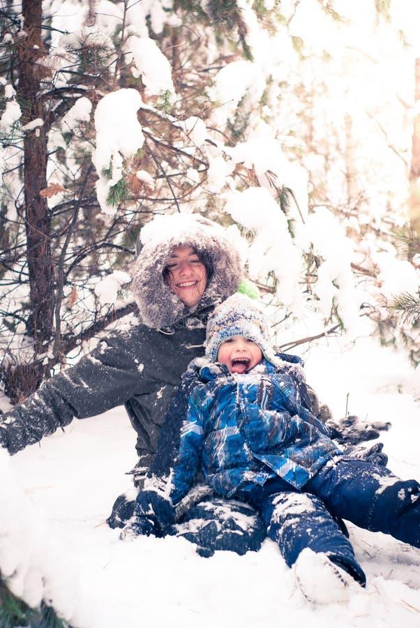 Fostra och behandla som ett barn pojken som spelar i den utomhus- vintern royaltyfri bild