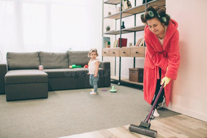 Fostra och behandla som ett barn tillsammans förlovat i hushållsarbete Hon tvättar golvet av golvmoppet Hemmafru och unge som gör royaltyfri foto