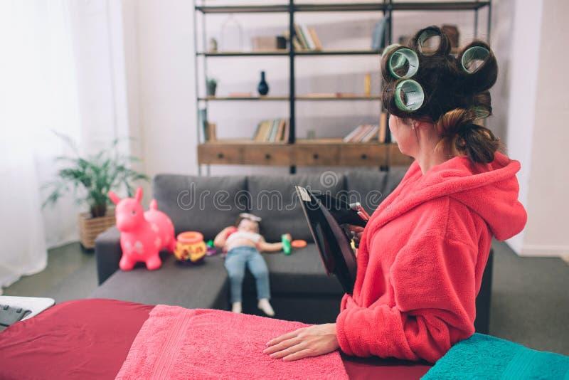 Fostra och behandla som ett barn tillsammans förlovat i hushållsarbetestrykningkläder Hemmafru och unge som gör läxa Kvinna med l royaltyfria foton