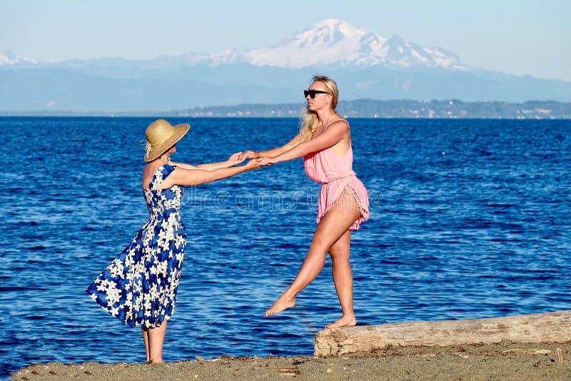Fostra och dottern på strand royaltyfri foto