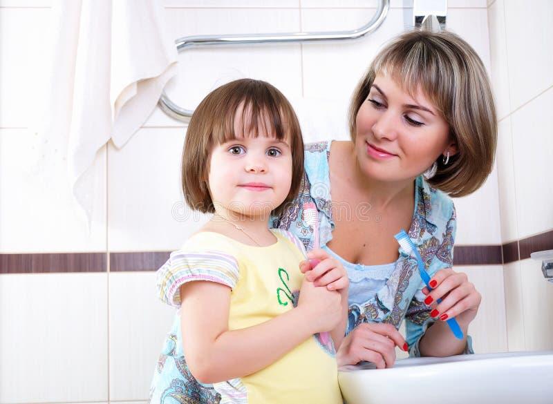 Fostra och dottern som borstar deras tänder royaltyfri bild