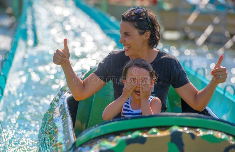 Fostra och hennes dotter som har gyckel i waterpark royaltyfri fotografi