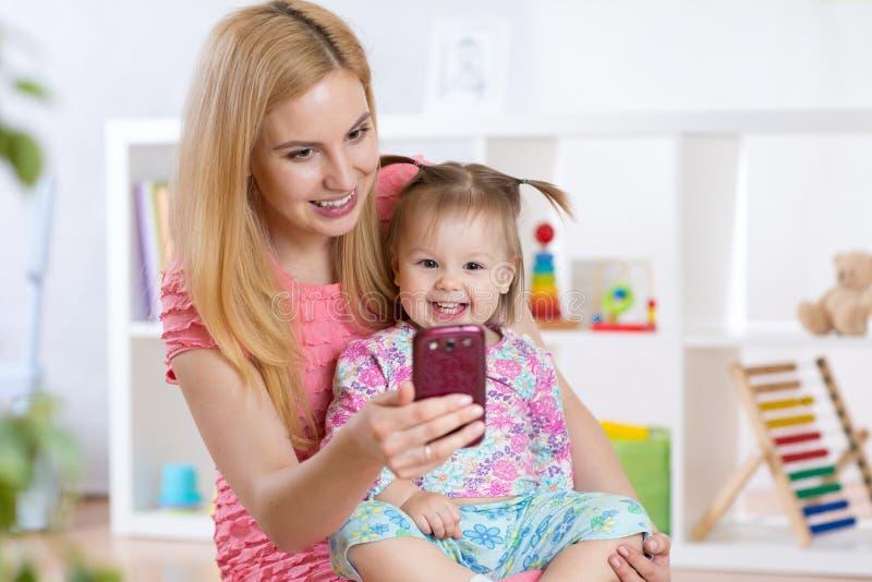 Fostra och hennes flicka för det lilla barnet som tar på selfie royaltyfria bilder