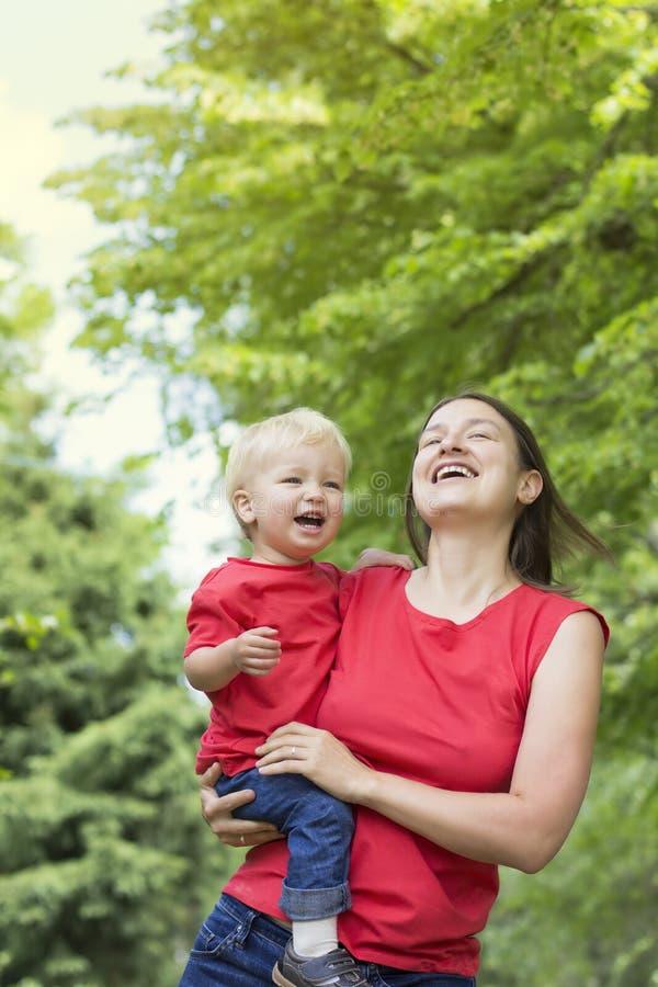 Fostra och hennes gulliga spela för litet barnson som är utomhus- Familjblickclo arkivfoton