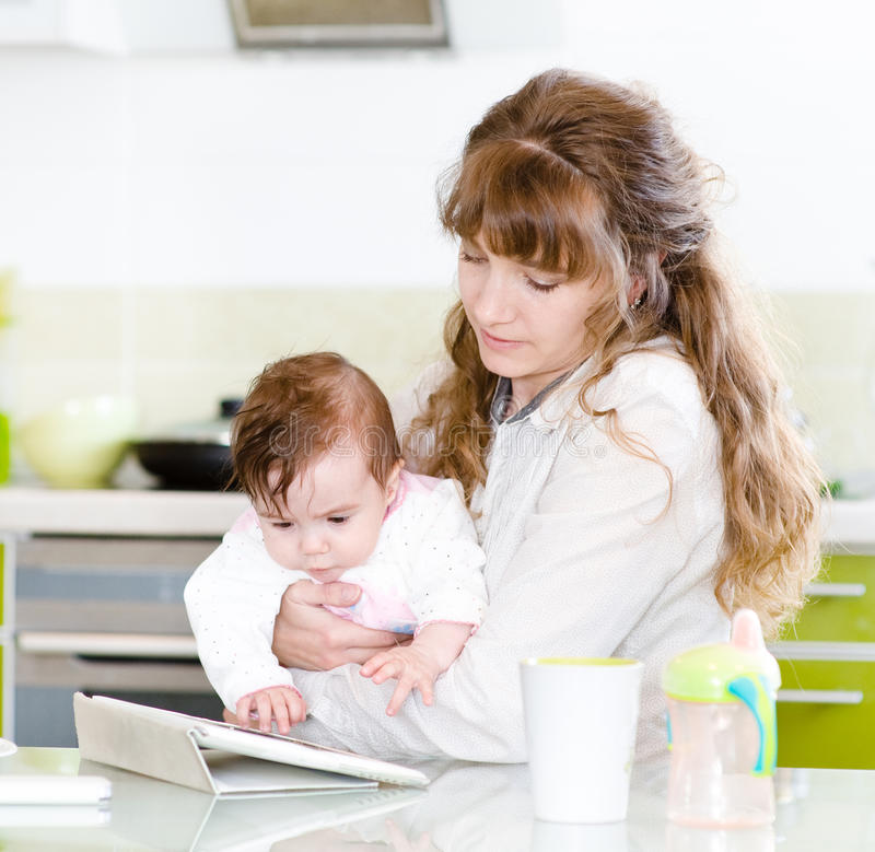 Fostra och hennes lilla dotter med minnestavlaPC royaltyfria bilder