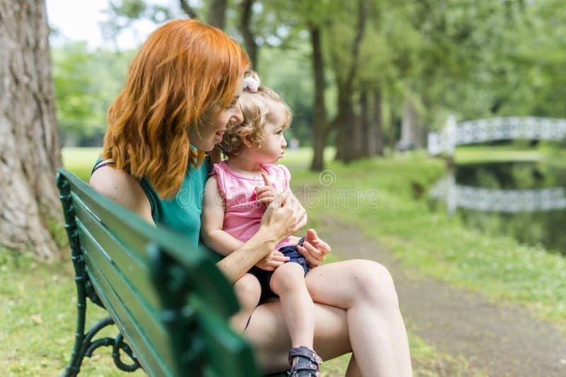 Fostra och hennes lilla dottersammanträde på en parkerabänk arkivfoto