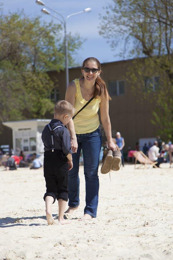 Fostra och hennes lilla son som går på sand i solig sommardag royaltyfria foton