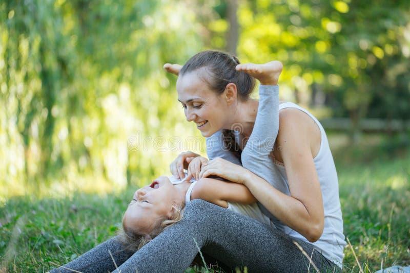 Fostra och hennes liten flicka på den gröna sommargräsängen som har gyckel royaltyfri foto