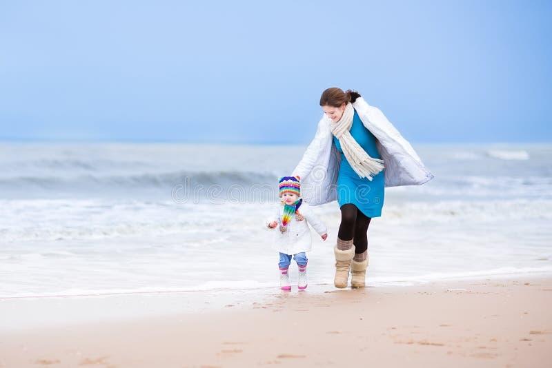 Fostra och hennes litet barndotterspring på stranden royaltyfri bild