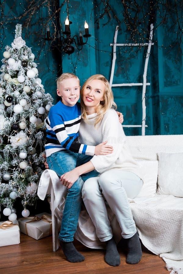 Fostra och hennes son hemma med en julgran royaltyfri bild