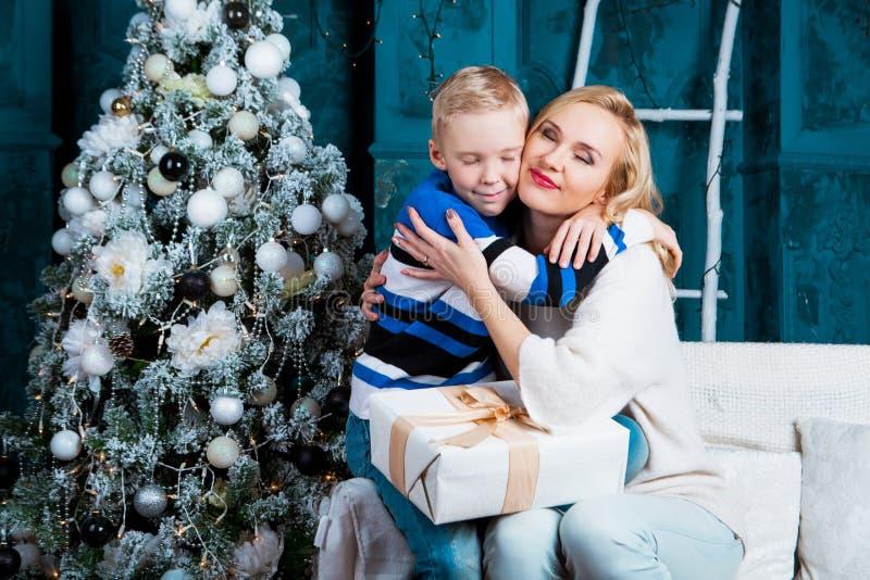 Fostra och hennes son hemma med en julgran fotografering för bildbyråer