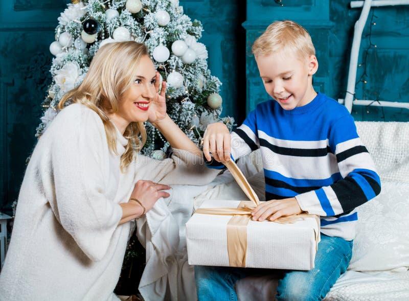 Fostra och hennes son hemma med en julgran royaltyfria bilder
