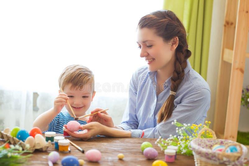 Fostra och hennes son som målar färgrika easter ägg fira easter familj Föräldern och ungen spelar inomhus Dekorerat hem och sprin arkivfoto