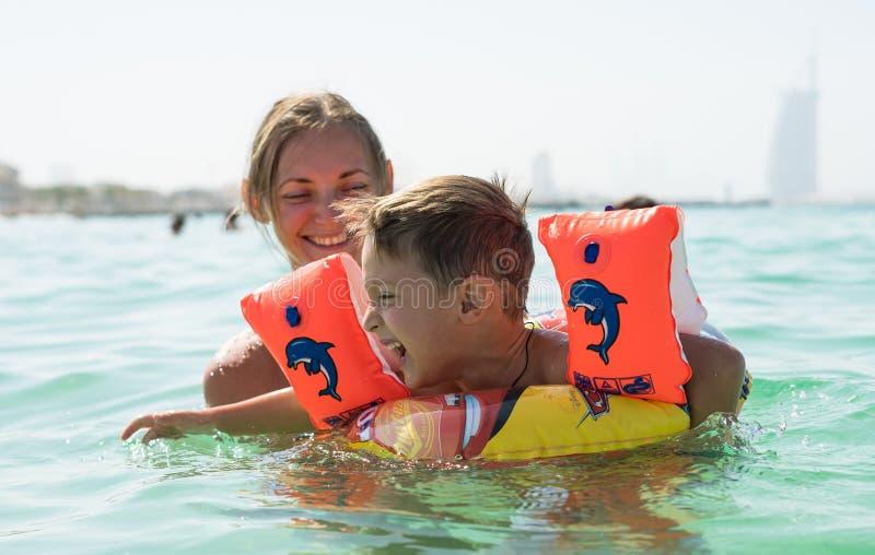 Fostra och hennes son som spelar och kör på stranden Begrepp av den vänliga familjen royaltyfria bilder