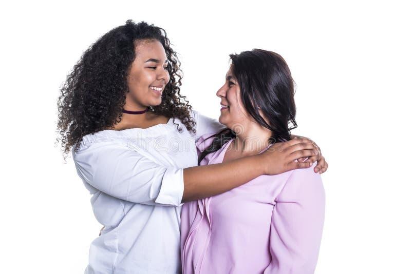 Fostra och hennes tonårs- dotter som isoleras på vit royaltyfri bild