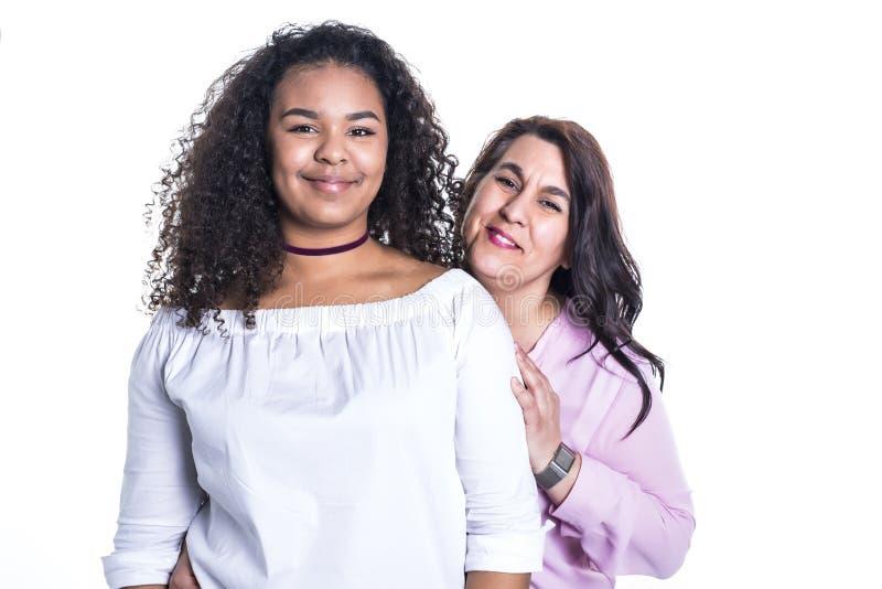 Fostra och hennes tonårs- dotter som isoleras på vit arkivfoton