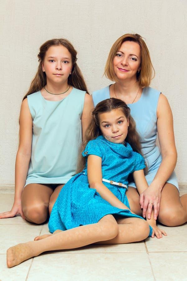 Fostra och hennes två döttrar som sitter på golvet arkivfoton