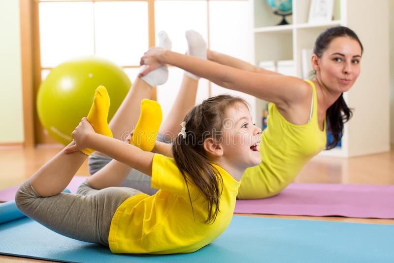 Fostra och lura i idrottshallmitten som gör sträcka konditionövning yoga royaltyfri bild