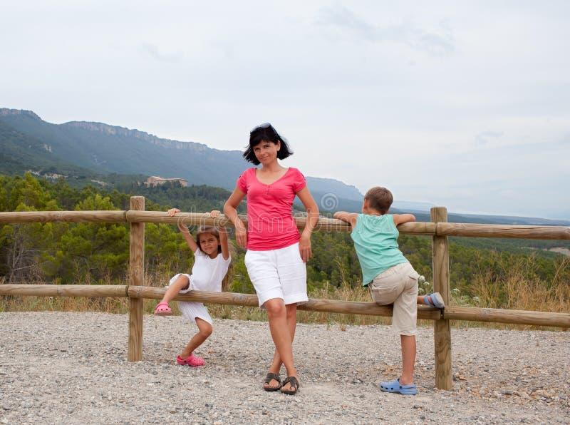 Fostra och två barn som lutar på ett staket arkivfoton