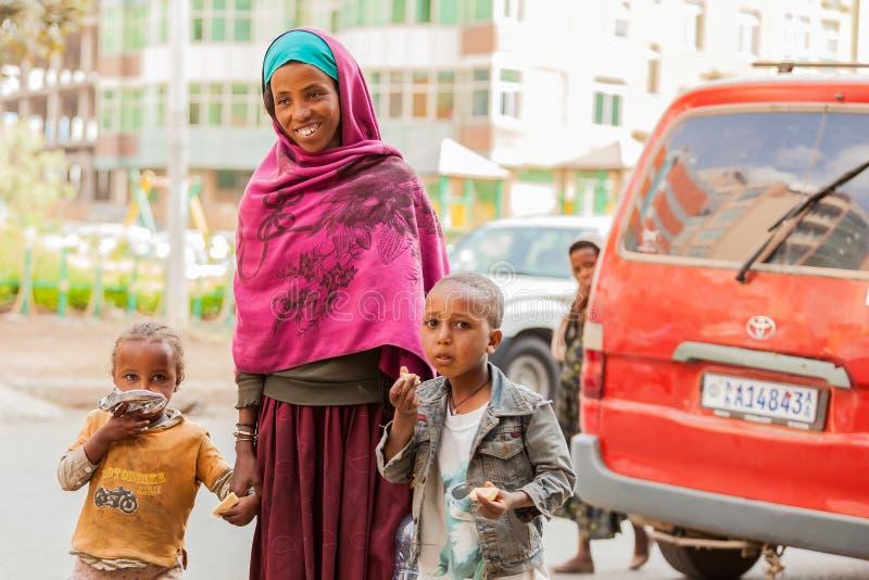 Fostra och två barn som rymmer händer på en tyst stadsgatawhi arkivfoto