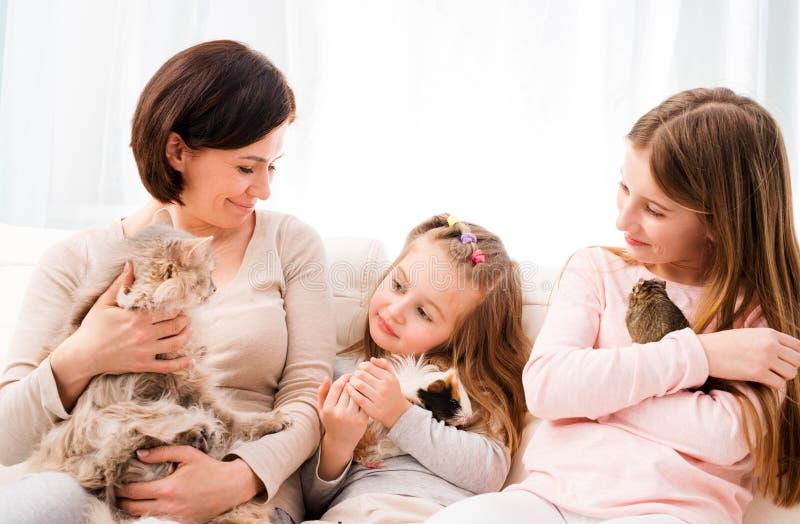 Fostra och två döttrar som rymmer deras favorithusdjur på händer royaltyfria bilder