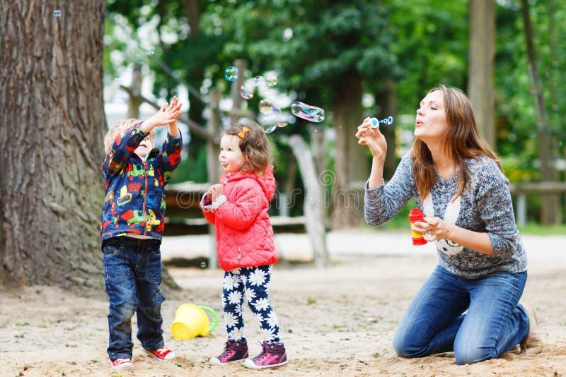 Fostra och två lilla barn som tillsammans spelar på lekplats royaltyfria foton