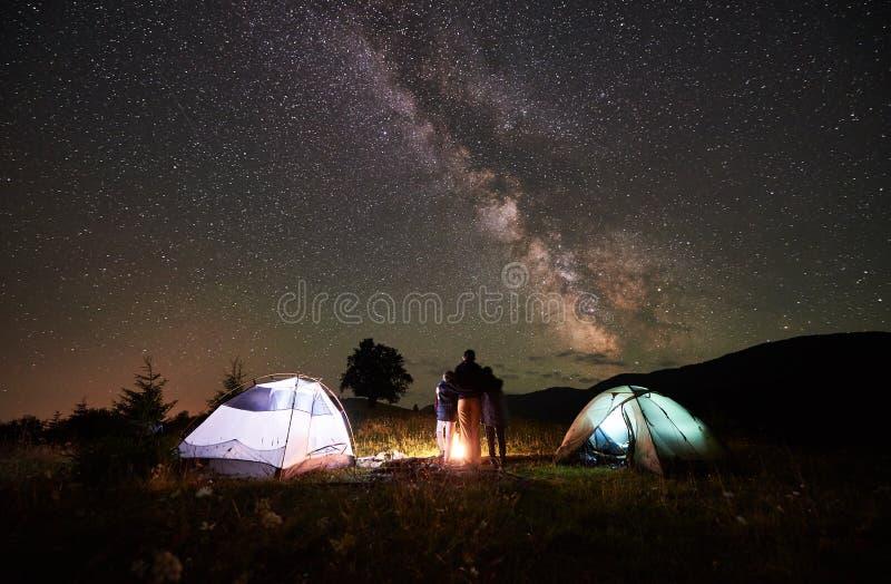 Fostra och två sonfotvandrare på att campa i berg under natthimmel mycket av stjärnor och den mjölkaktiga vägen royaltyfri foto